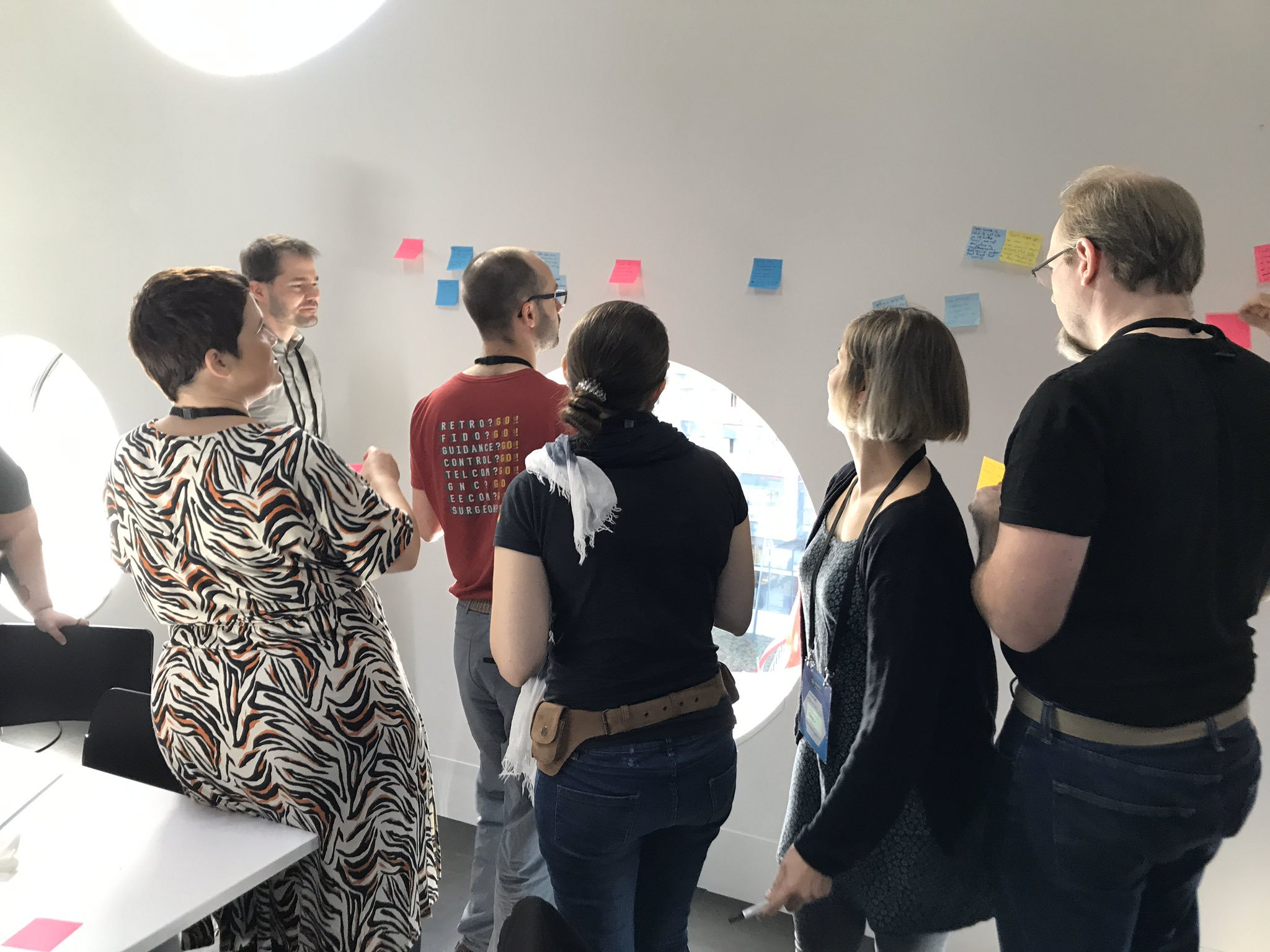 A group of people at #mozfest, clustered around a wall with post-it notes on